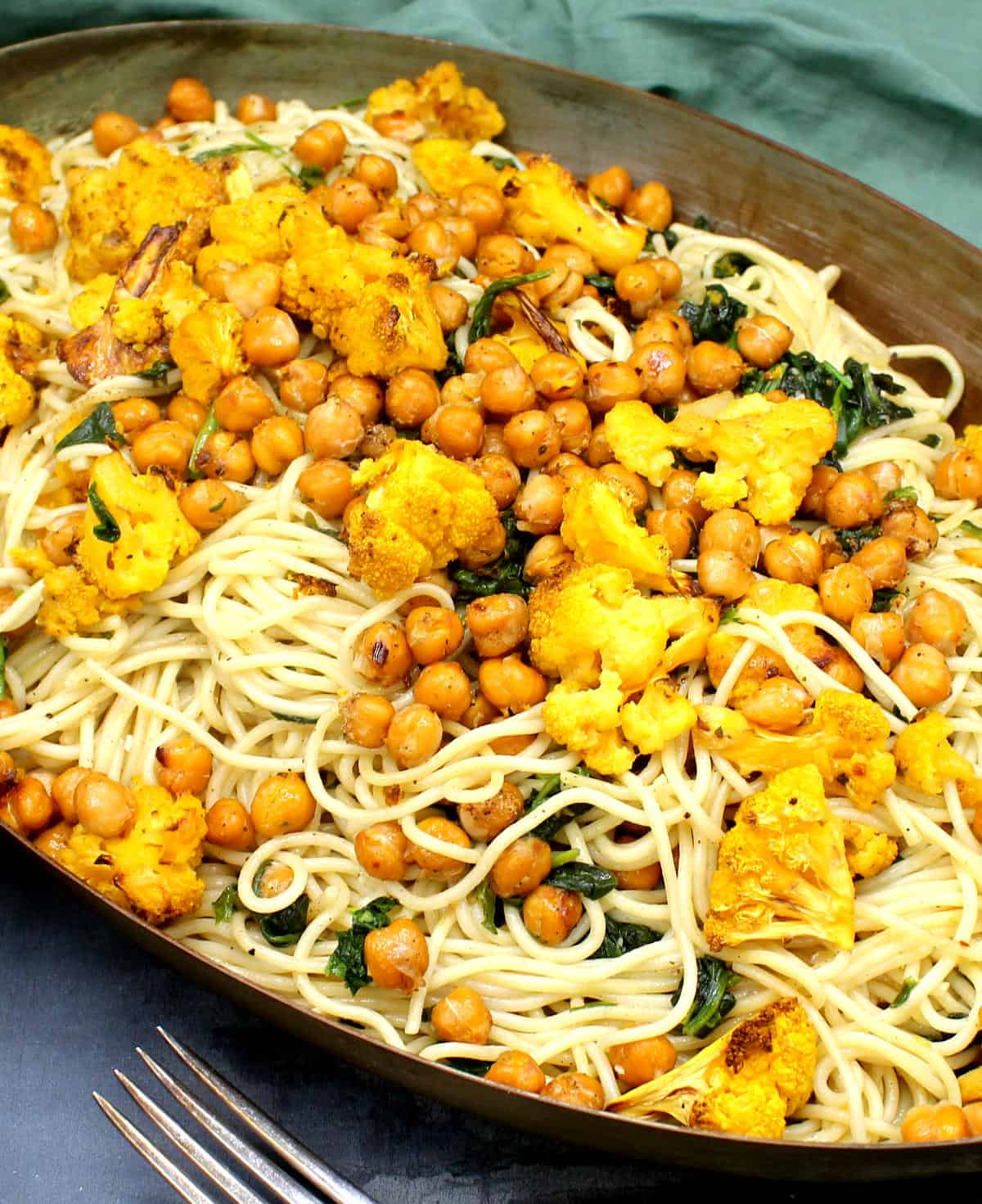 Front closeup shot of a pan with pasta tossed with roasted chickpeas, cauliflower and spinach with garlic, lemon and spices and herbs.