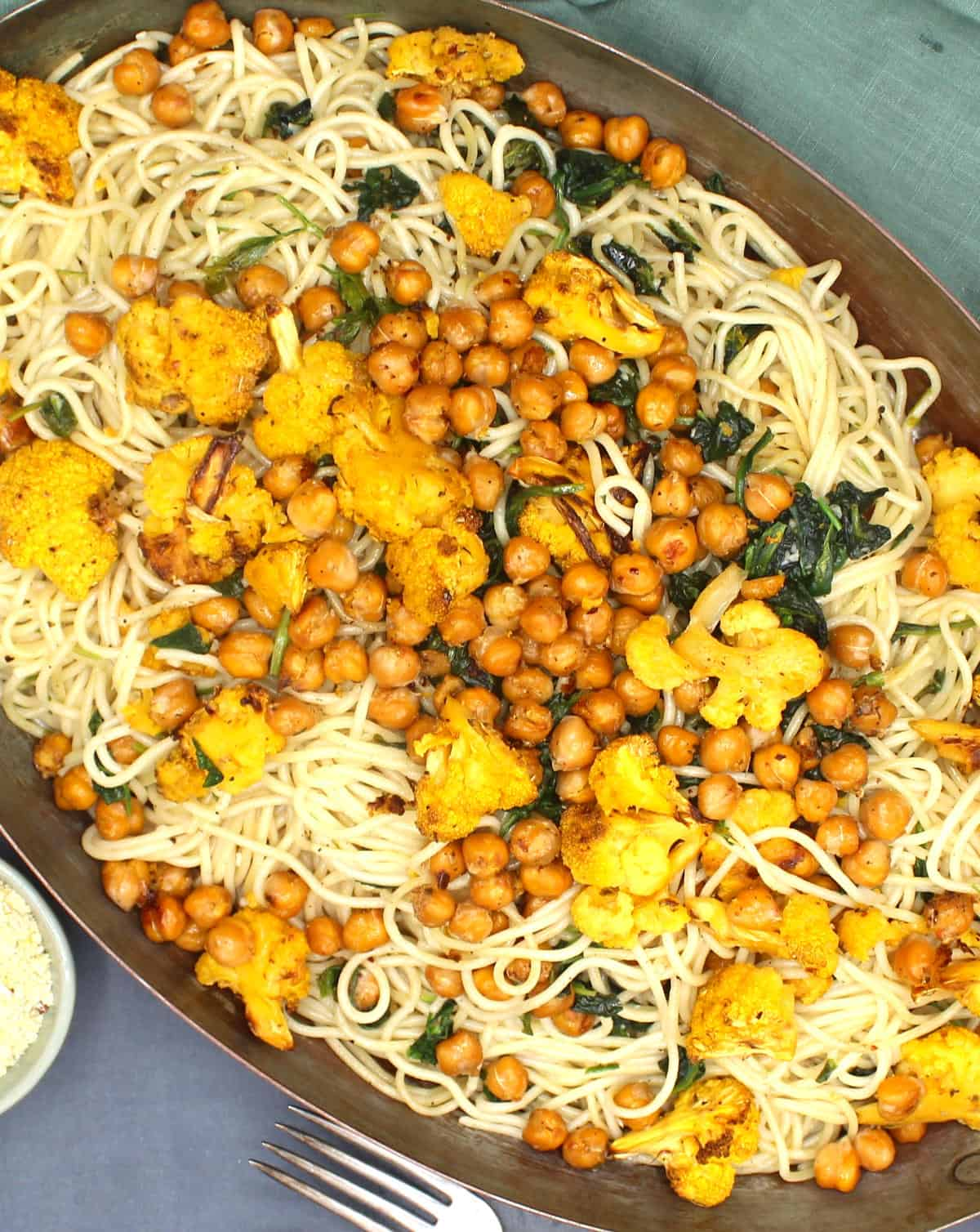 Overhead closup of spaghetti pasta with roasted cauliflower, chickpeas and spinach in a copper pan.