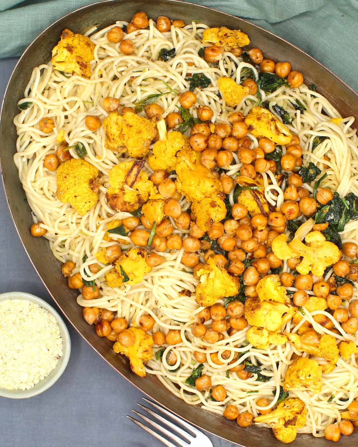 Overhead shot of a pan with spaghetti tossed with roasted chickpeas, cauliflower and spinach with vegan cashew parmesan on the side.