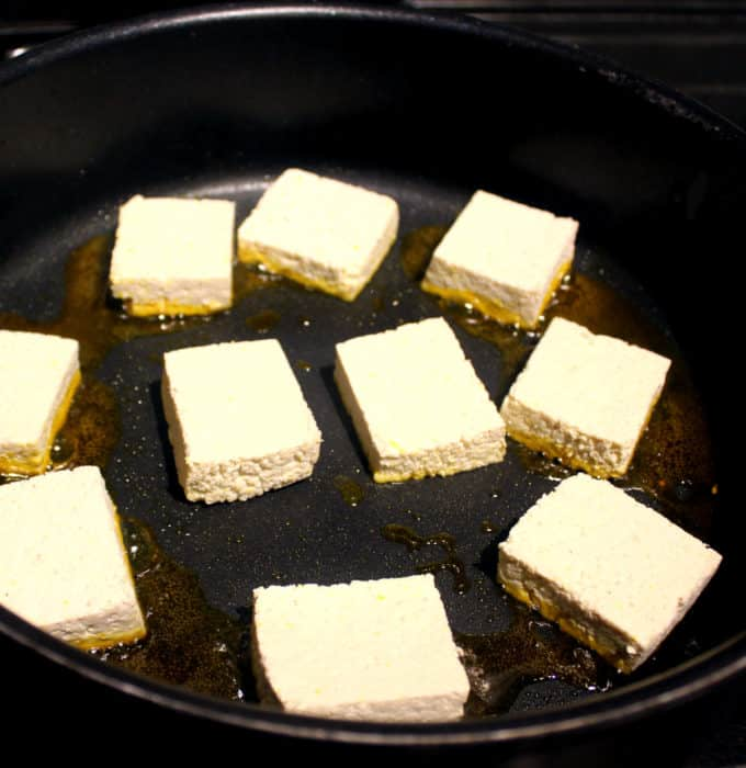 tofu cubes in a frying pan with red palm oil