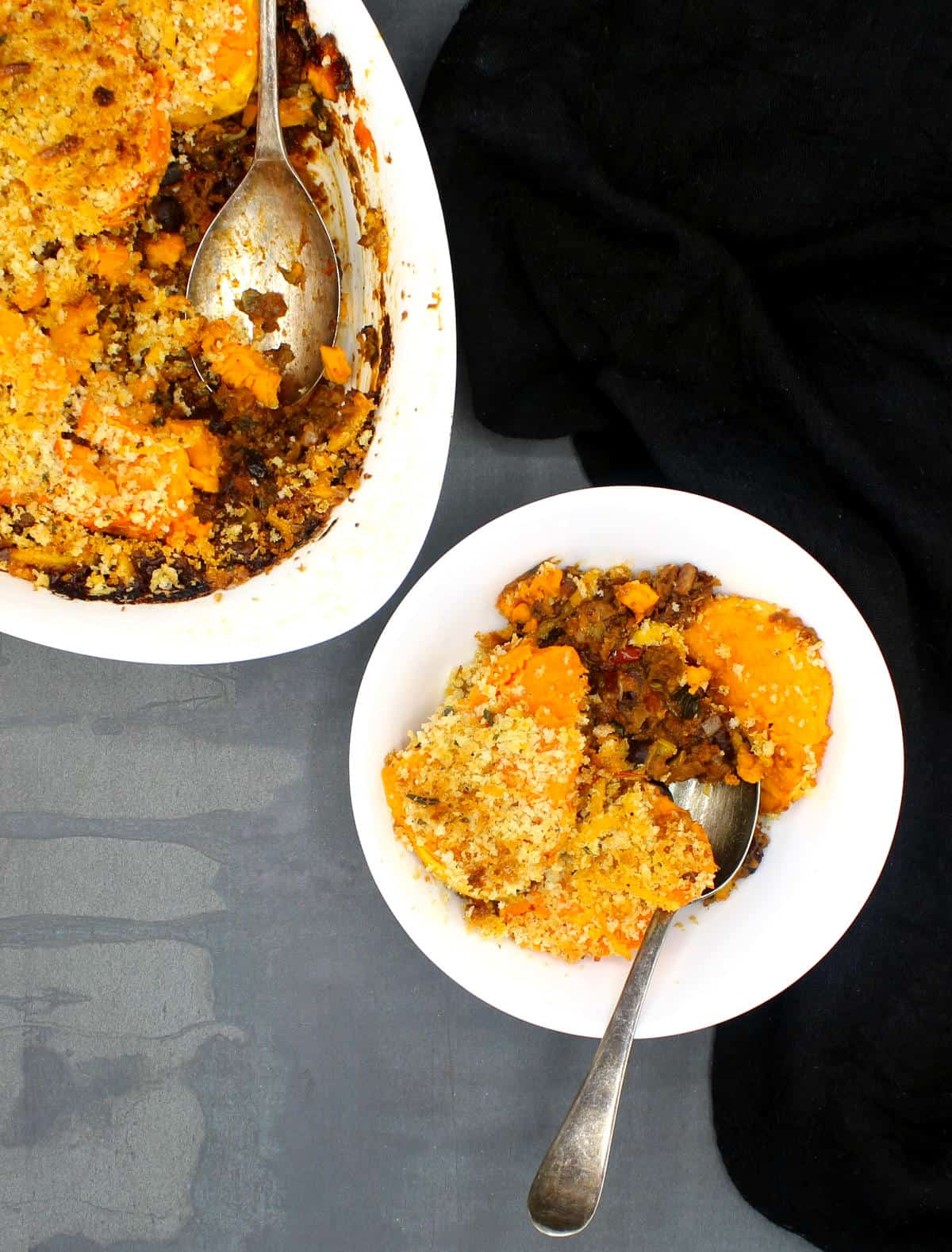 A vegan breakfast sweet potato chili bake in a white bowl and casserole dish with a black cheesecloth on gray background.