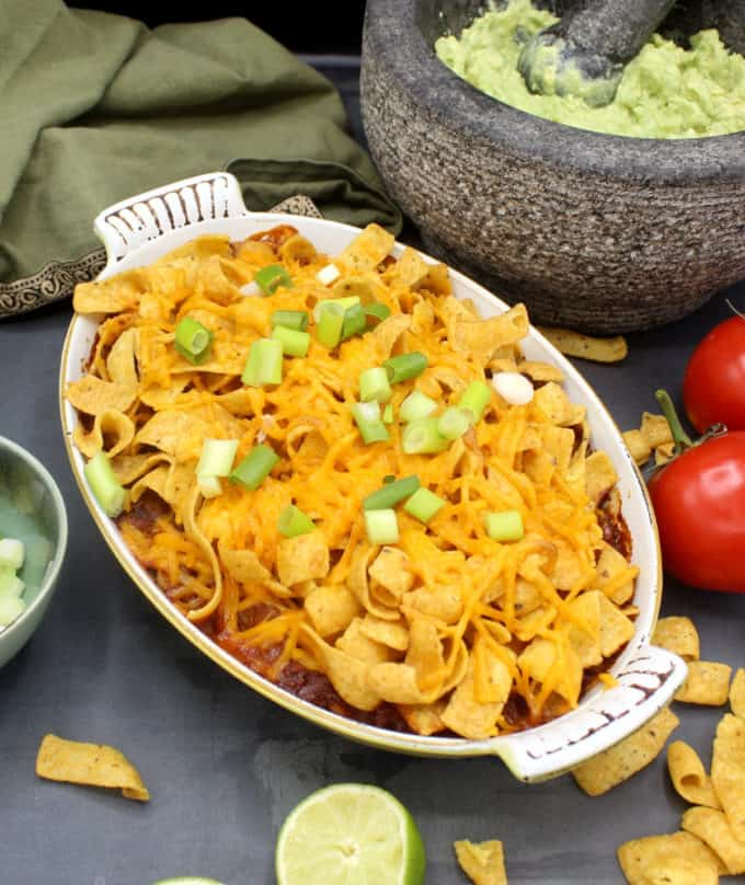 Vegan Frito pie in a baking dish with scallions, tomatoes and guacamole