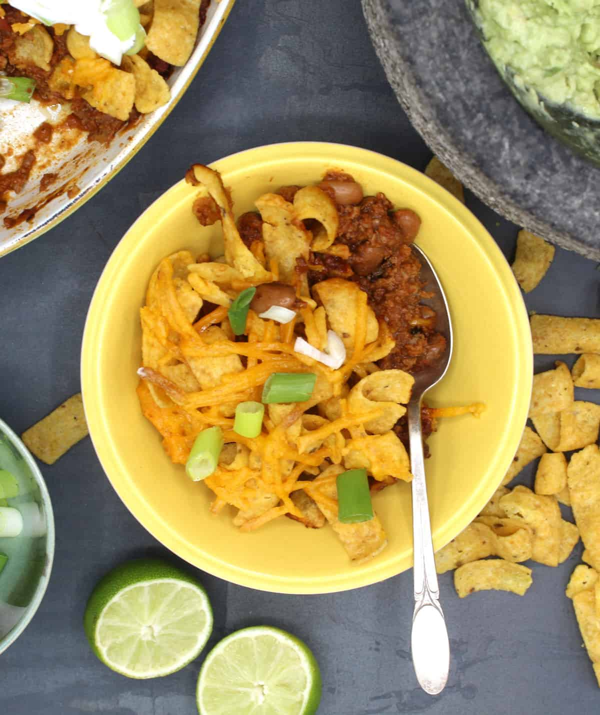 Vegan Frito Pie in a yellow bowl with guacamole and limes.