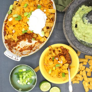 Vegan frito pie in baking dish and bowl with guacamole and scallions