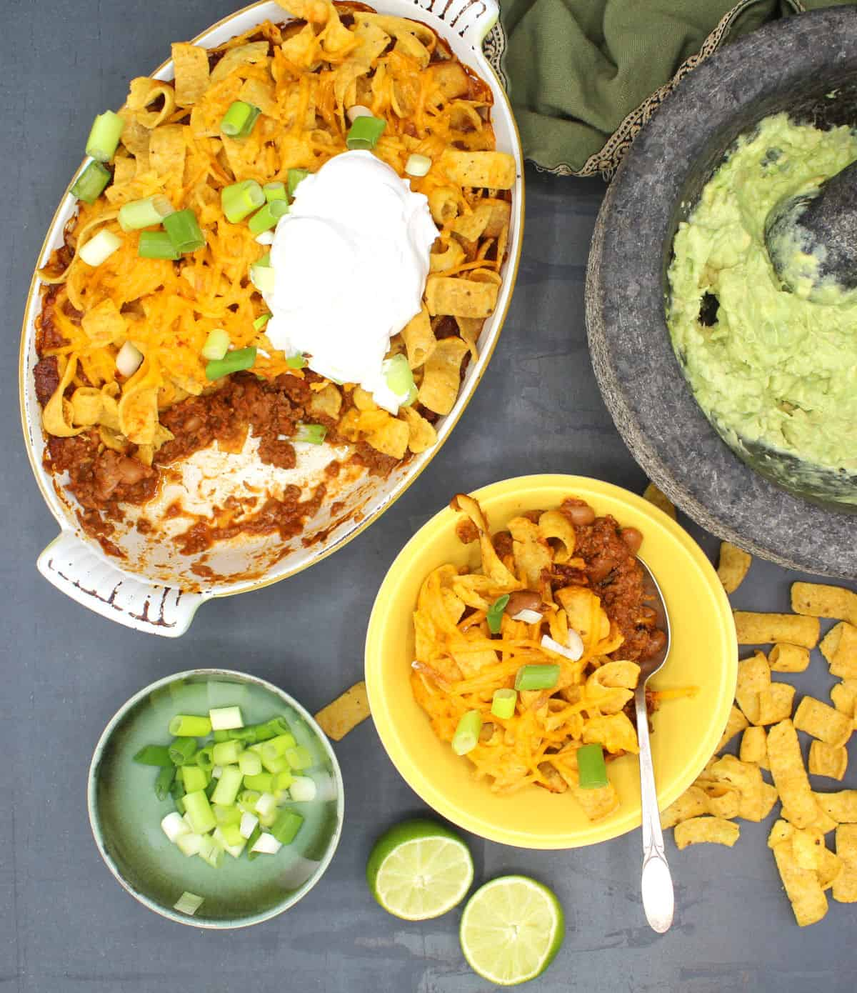Vegan Frito pie in baking dish and bowl with vegan sour cream, scallions and guacamole.