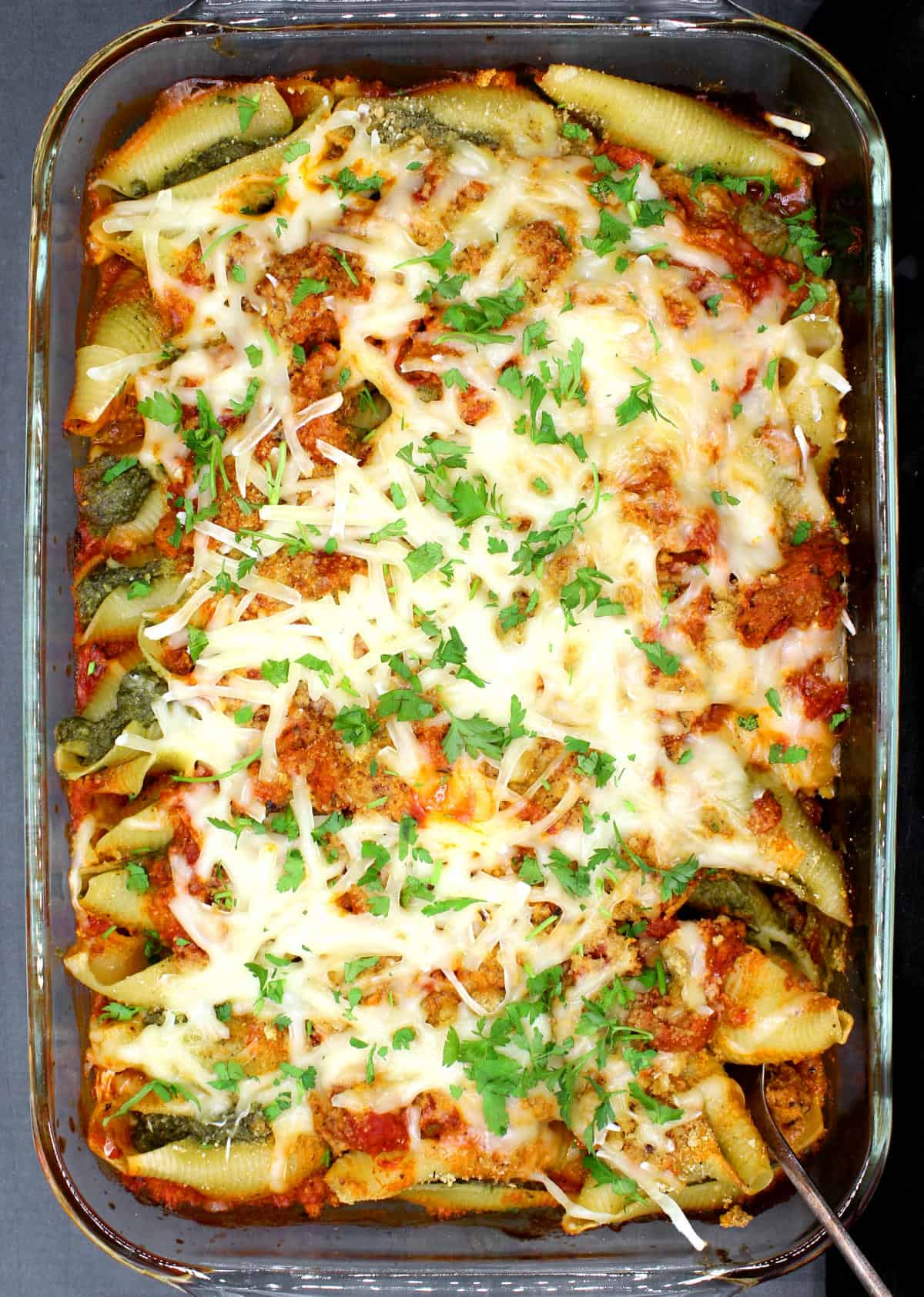 A closeup of a casserole with cheesy vegan stuffed shells with meaty marinara sauce and mozarella shreds.