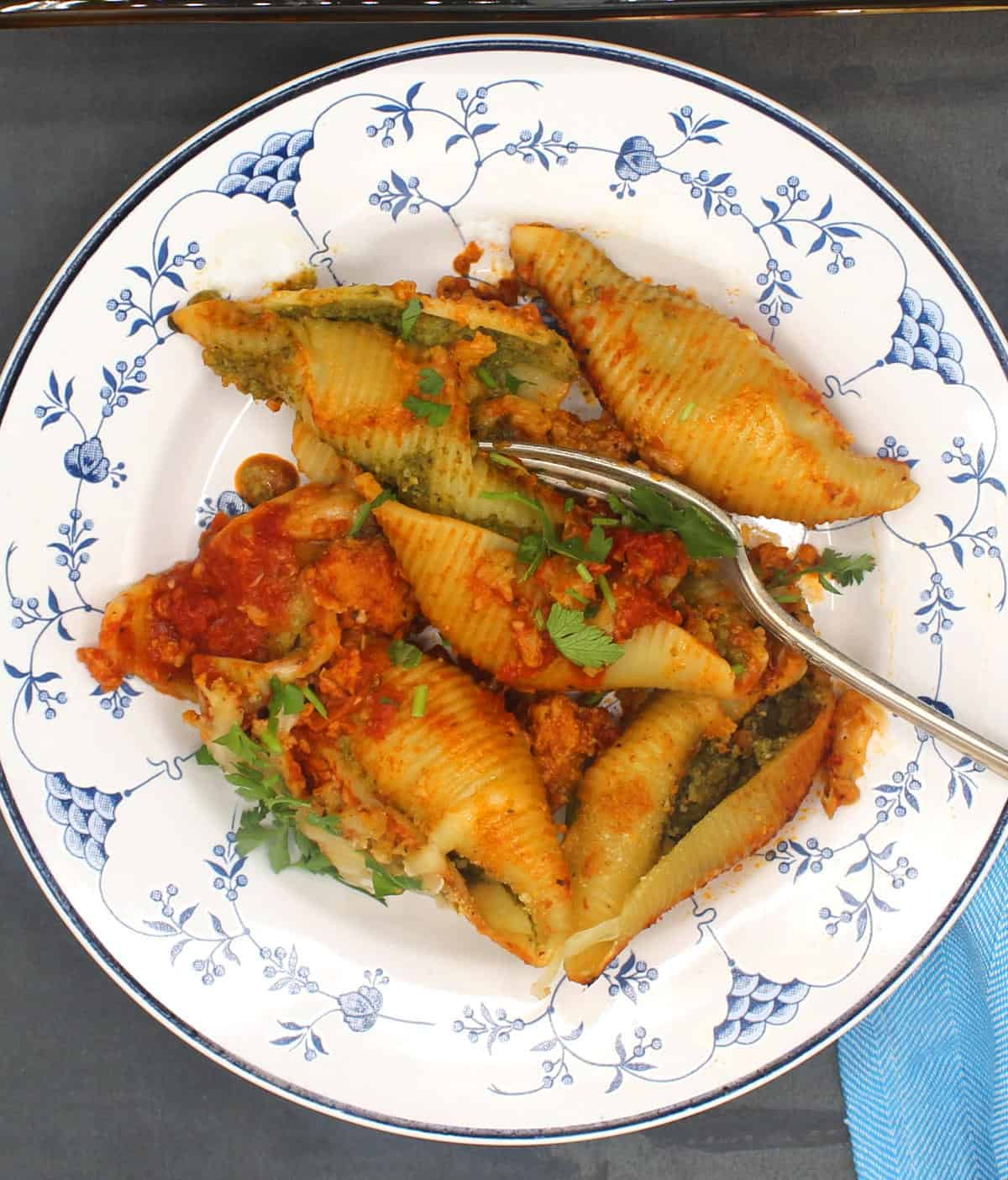 Stuffed pasta shells with spinach ricotta stuffing, marinara and parsley in an Italian blue and white dish.