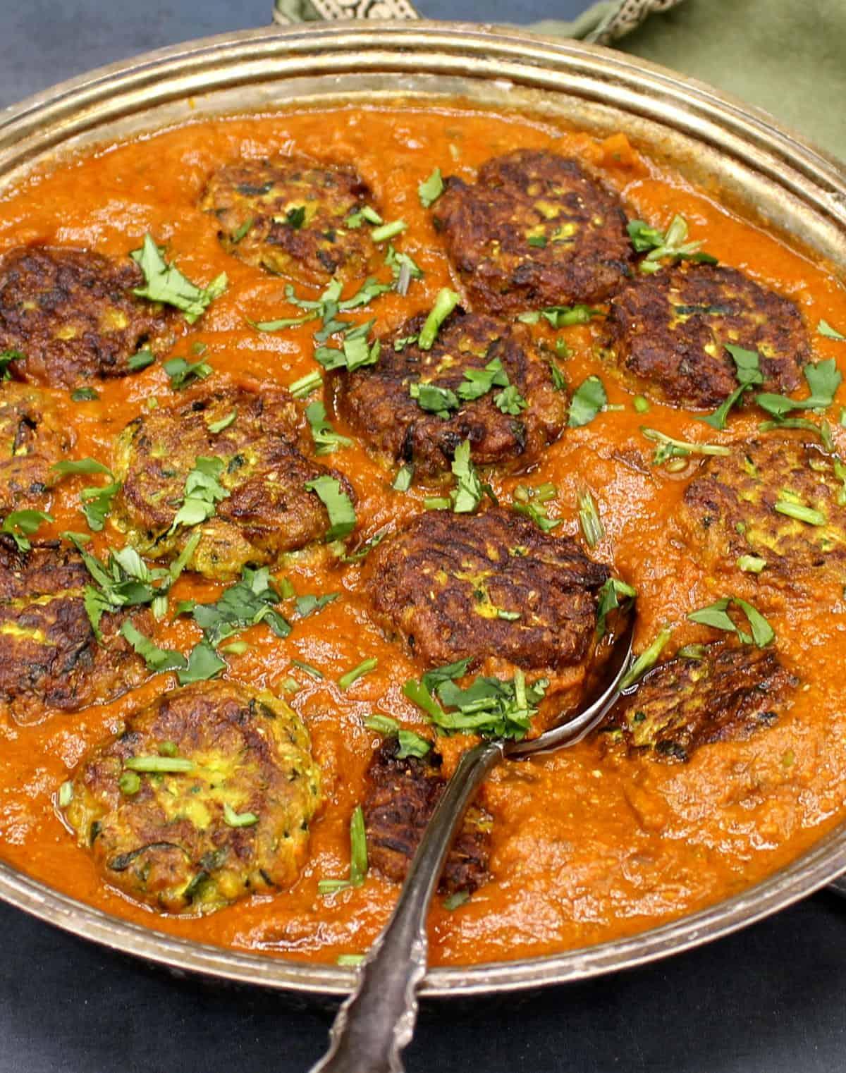 Close up of zucchini kofta curry with zucchini kofta ballls in an orange sauce garnished with cilantro.