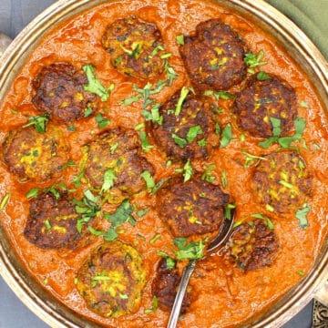 Zucchini Kofa Curry in a silver serving dish with cilantro garnish