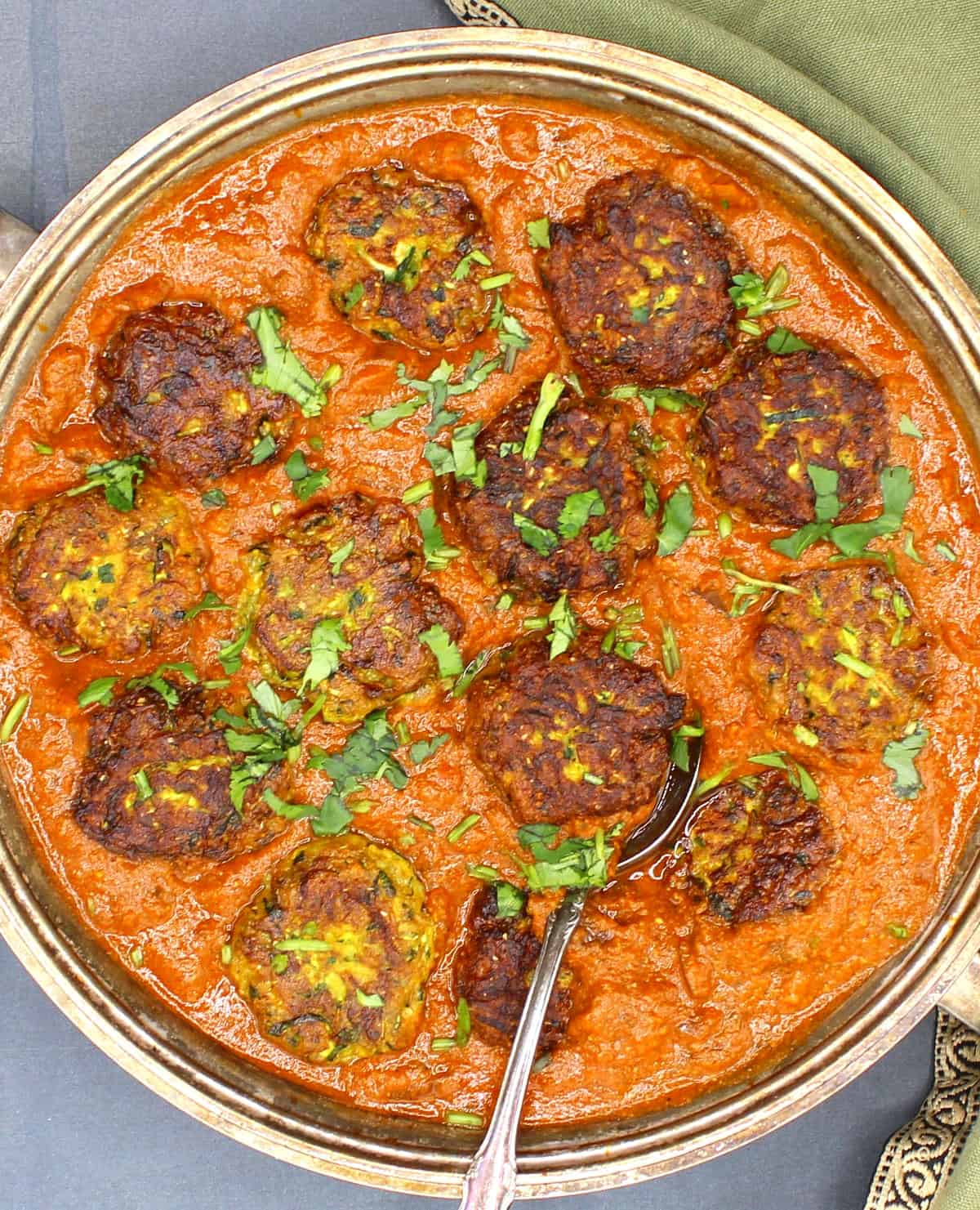 Overhead closeup of zucchini kofta curry with cilantro garnish and a spoon in a silver serving dish with a green napkin.