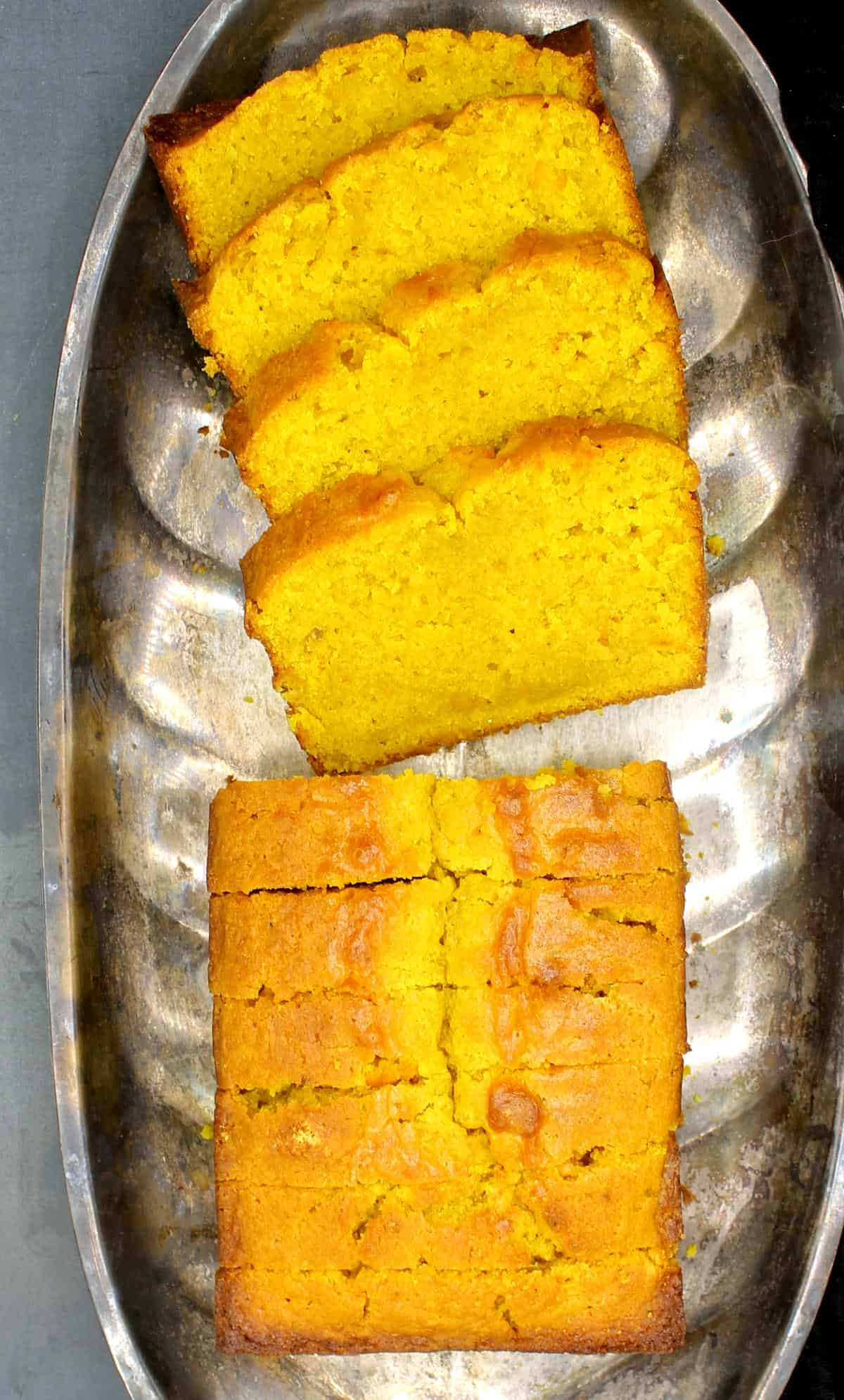 A sliced vegan cardamom turmeric cake in a silver serving tray