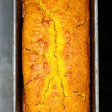 A loaf of vegan cardamom turmeric cake in loaf pan