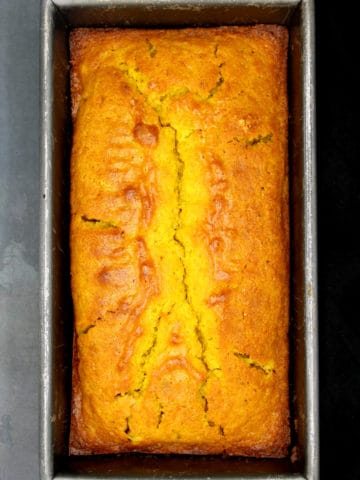 A loaf of vegan cardamom turmeric cake in loaf pan