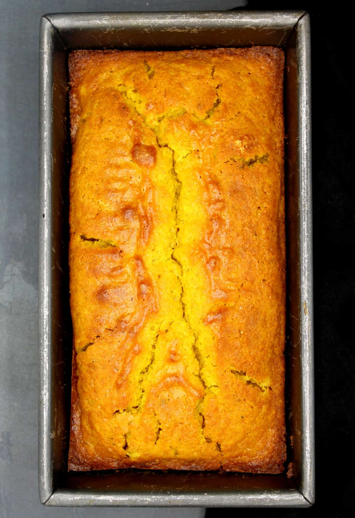 A golden vegan turmeric cake with cardamom freshly baked, in a loaf pan