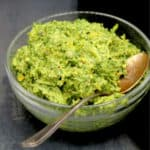 Carrot top pesto in a glass bowl with a silver spoon on black background