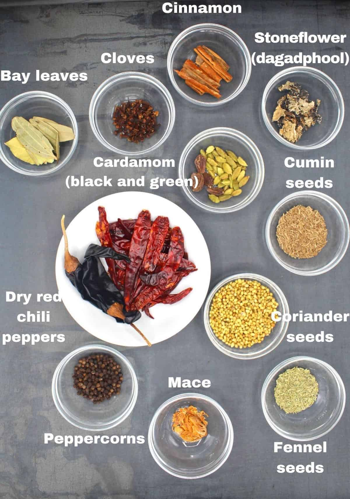 All of the whole spices for garam masala in bowls, including cinnamon, cloves, cardamom, stoneflower, fennel seeds, peppercorns, bay leaves, coriander seeds, red chili peppers, mace and coriander seeds.