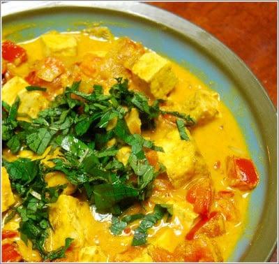 Tofu patia with cilantro, tomatoes, coconut milk and tofu ina  blue and brown bowl.