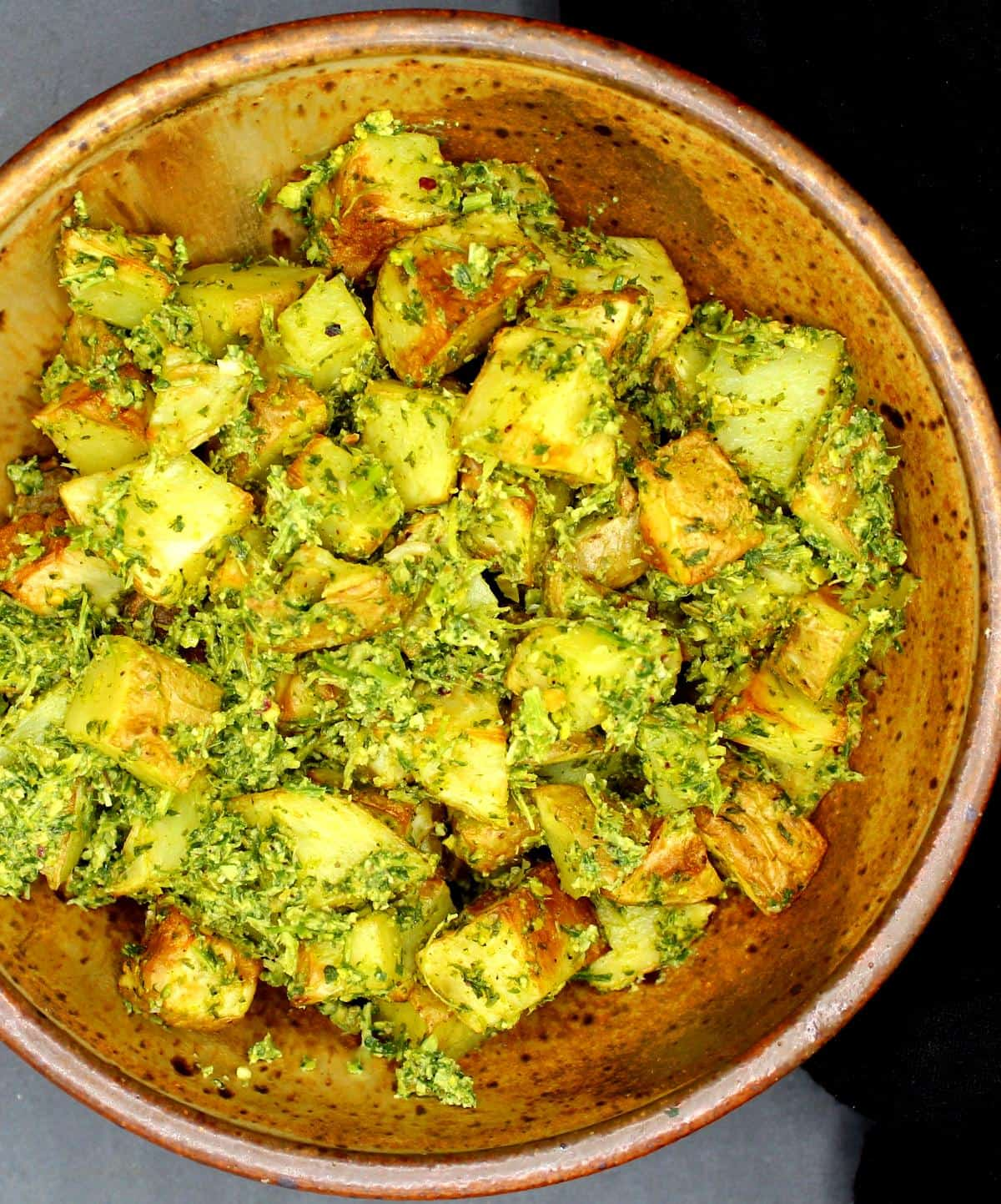 Potatoes tossed with vegan carrot pesto in a speckled bowl.