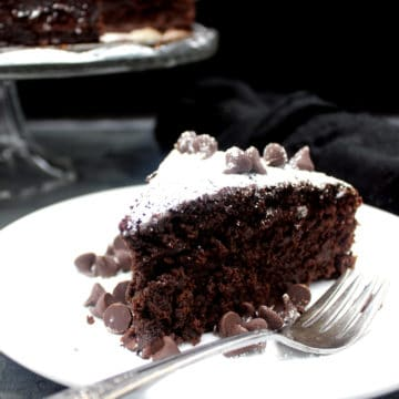 Slice of vegan chocolate whiskey cake with chocolate chips on a white plate with fork