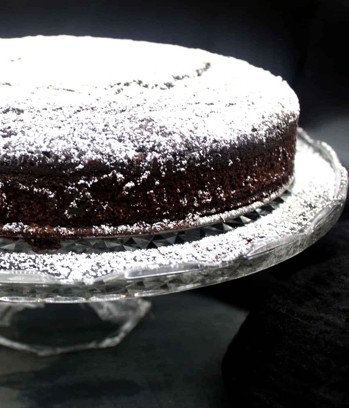 Front partial shot of a vegan chocolate whiskey cake dusted with powdered sugar on a decorative crystal cake stand.