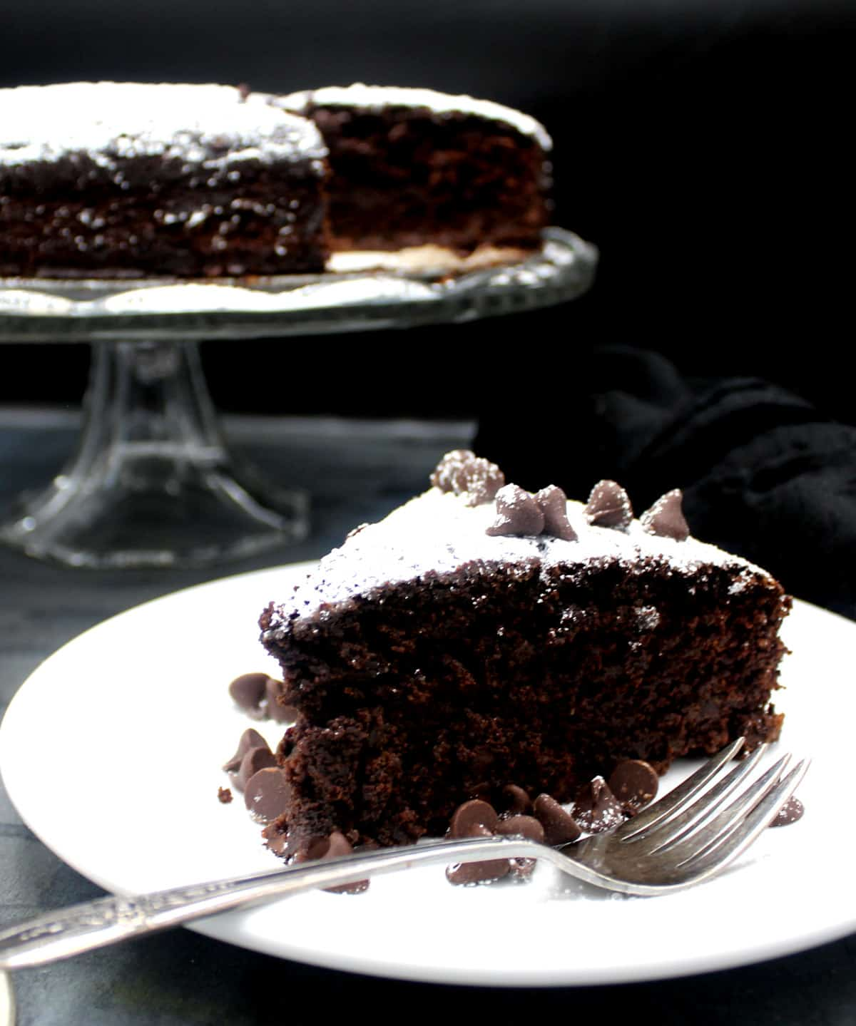 A slice of Irish chocolate whiskey cake on a plate with chocolate chips and a fork with the full cake in background on a glass cake stand.