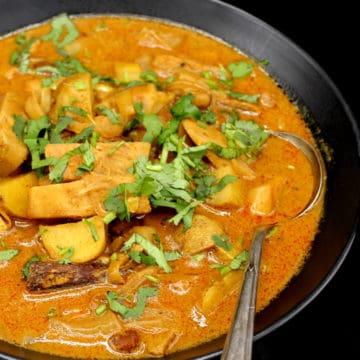 A closeup of vegan Thai massaman curry in a black bowl