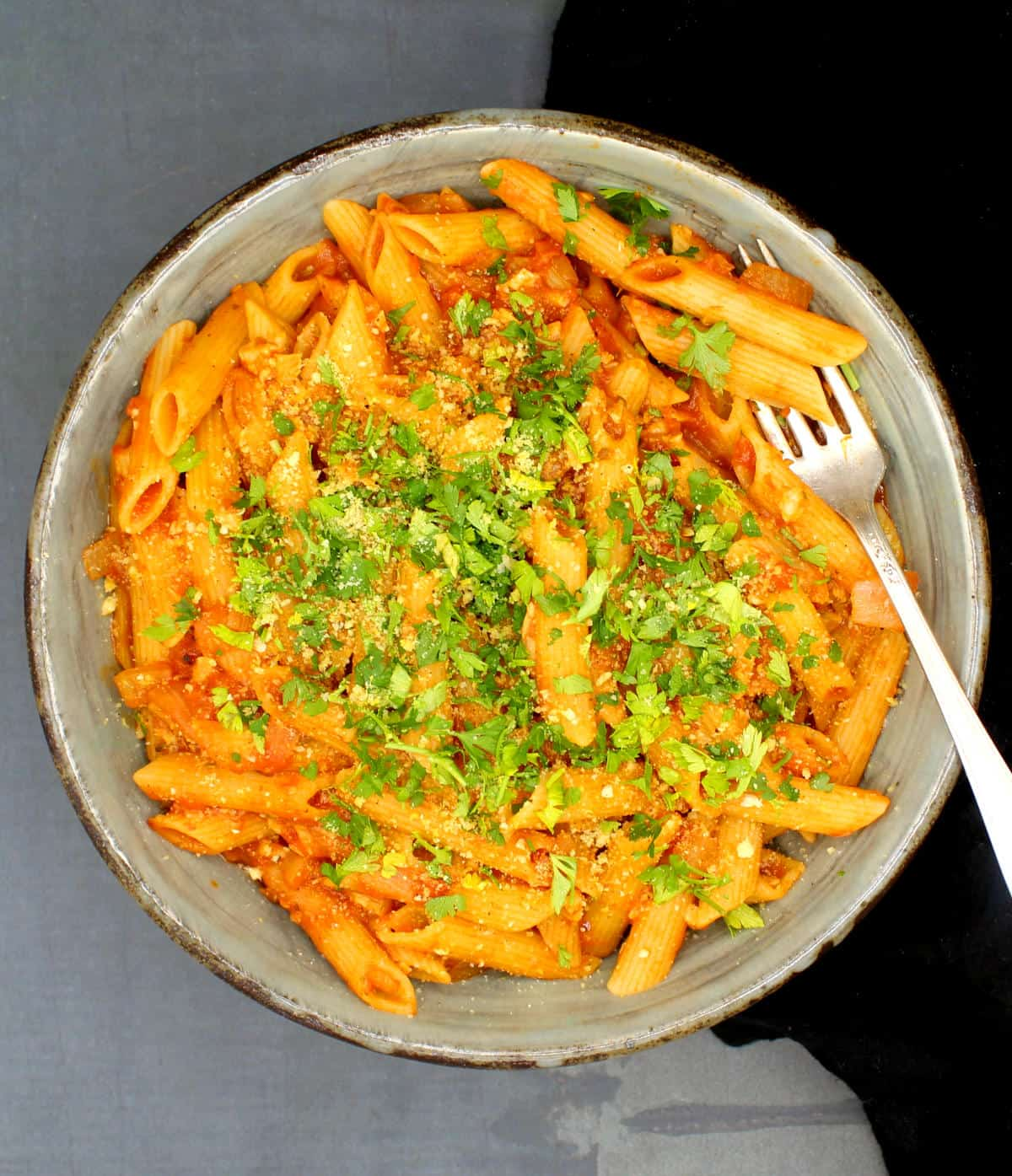 Vegan Pasta Amatriciana in a big bowl with penne pasta, tomato sauce, parsley and cashew parmesan.