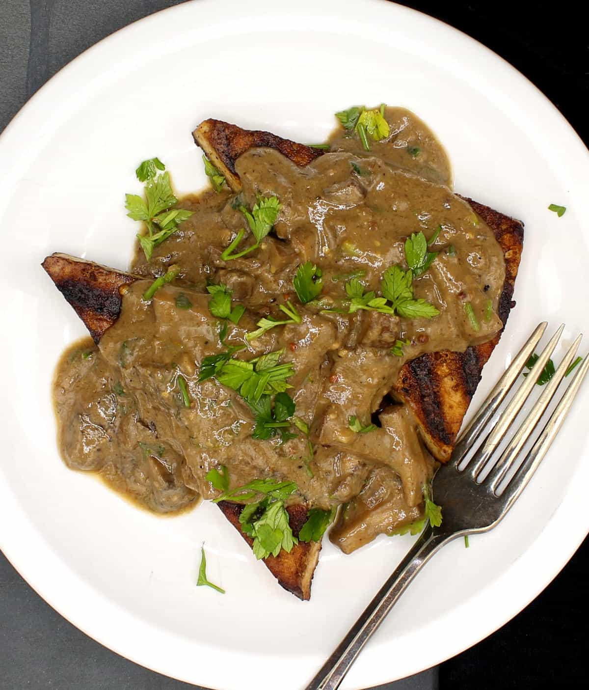 Vegan whisky steaks smothered ina  creamy mushroom sauce on white plate with a fork,