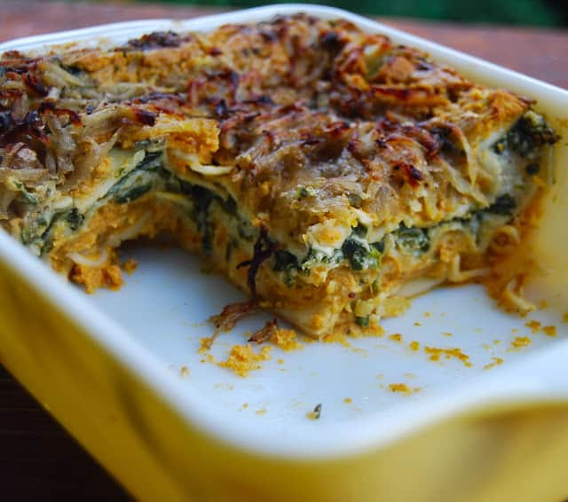Photo of a sliced vegan pumpkin spinach lasagna for two in a yellow and white baking dish.