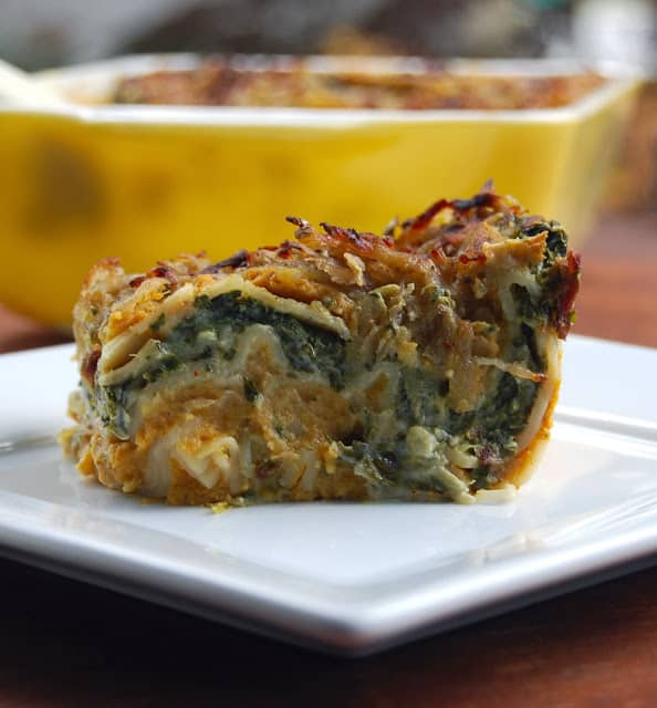 Photo of a delicious slice of pumpkin spinach lasagna on a white square plate.
