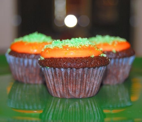 Photo of halloween cupcakes with orange and green icing and sugar.