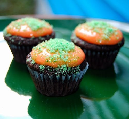 Photo of small Halloween cupcakes decorated with orange icing and green sugar.