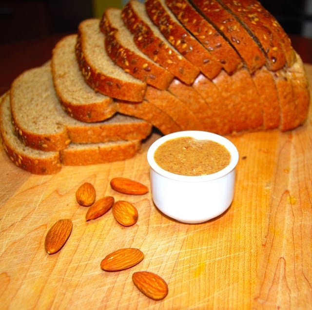 Photo of almond butter in a white cup with a whole wheat bread in background.