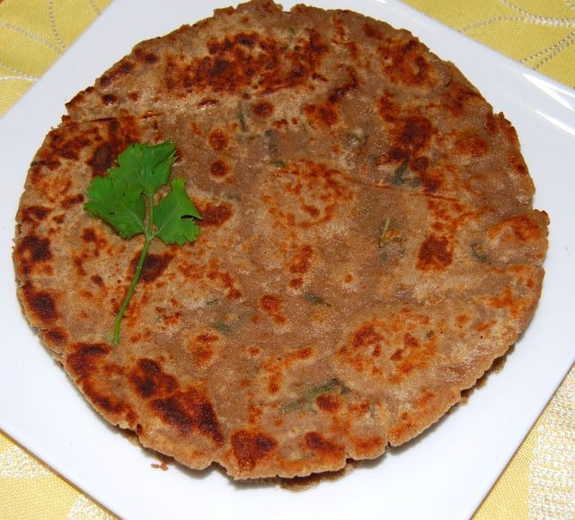 Photo of a stack of arbi parathas in a white square plate.