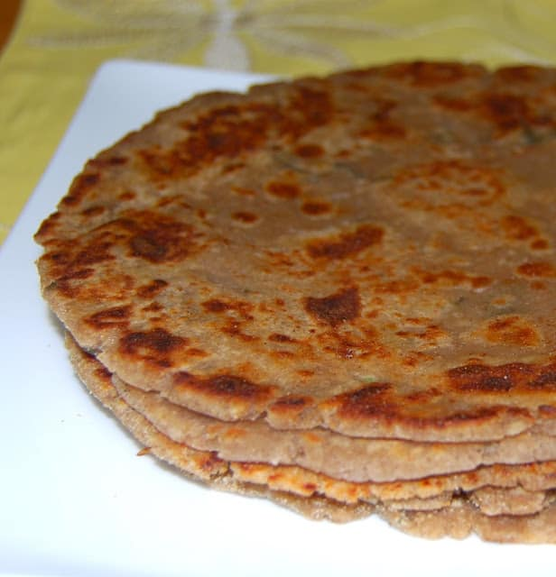 Photo of arbi parathas or colocasia parathas stacked in a plate.