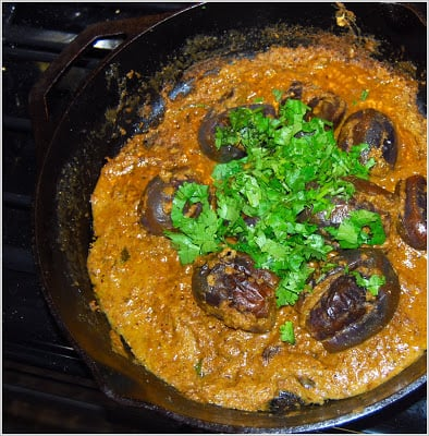 Photo of baghare baingan with a cilantro garnish in a cast iron skillet.