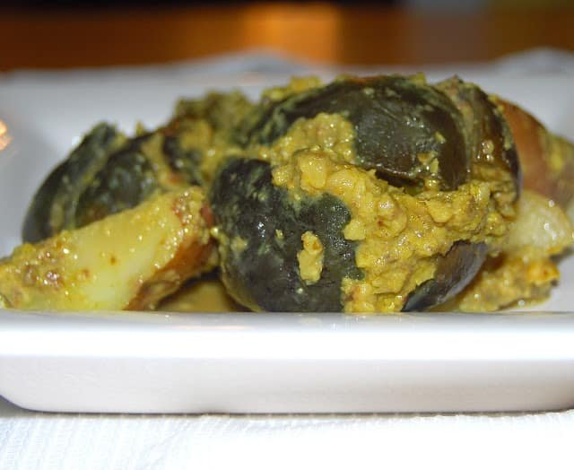 Photo of stuffed Indian eggplant on a white dish.
