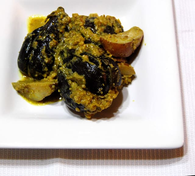 Photo of stuffed Indian eggplants in a spicy gravy on a white square plate.