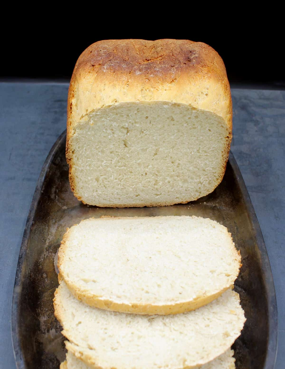 A gorgeous sourdough bread machine loaf, sliced, on a silver serving tray on a gray background.