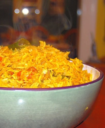 Photo of steaming hot cabbage rice in a green and white bowl.