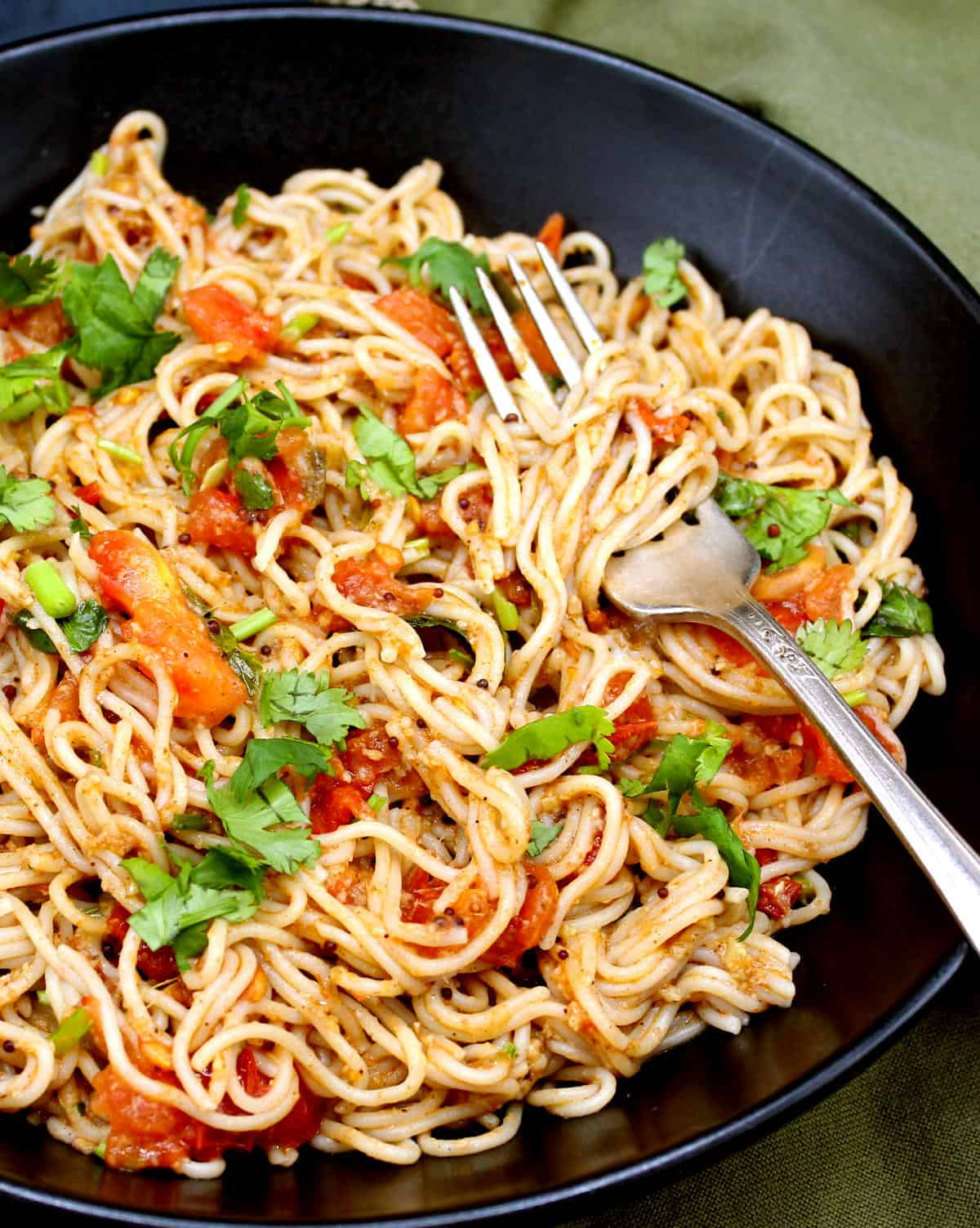 Photo of instant garlic and chili ramen noodles in a black bowl with tomatoes, cilantro and a fork.