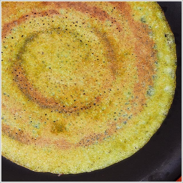 Photo of a south Indian dosa called an adai made with cilantro, lentils and rice.