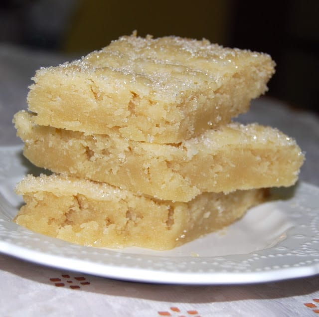 Photo of three vegan coconut shortbread cookies stacked on a decorative white plate.