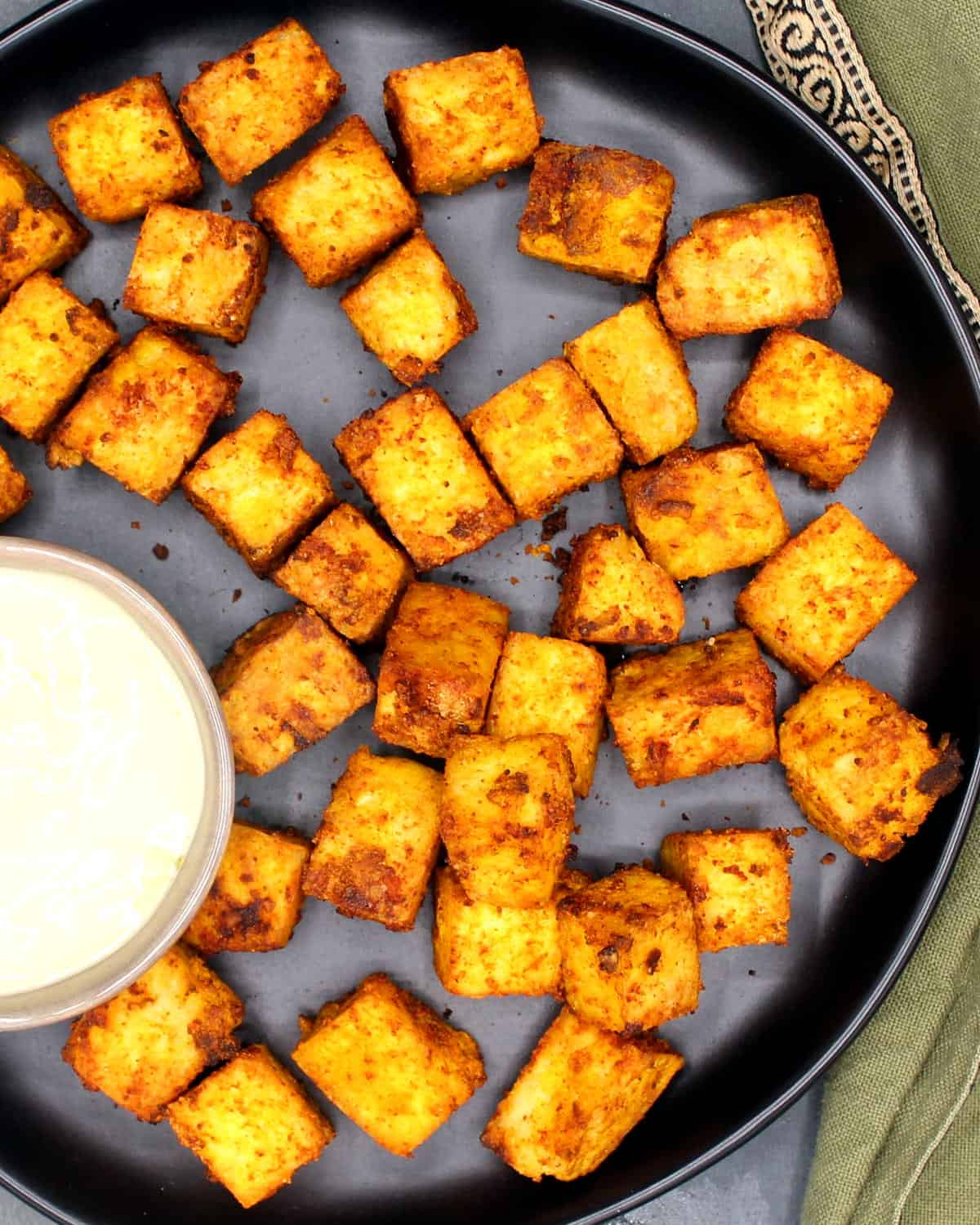 Photo of crispy air fried tofu cubes on a black plate with a mayo dipping sauce.