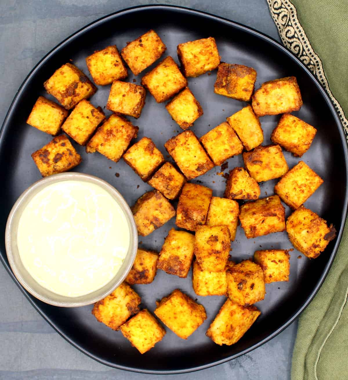 Photo of air fryer tofu cubes on a black plate with a creamy vegan mayo dipping sauce and a green napkin.