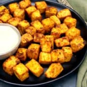Photo of crispy air fryer tofu cubes baked in an air fryer with a bowl of vegan mayo