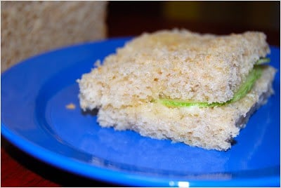 Photo of a cucumber sandwich on a blue plate.