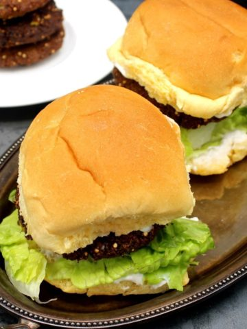 Photo of falafel burgers with mayo and lettuce on a silver tray