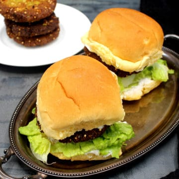 Falafel burgers on a silver tray with more burger patties in background