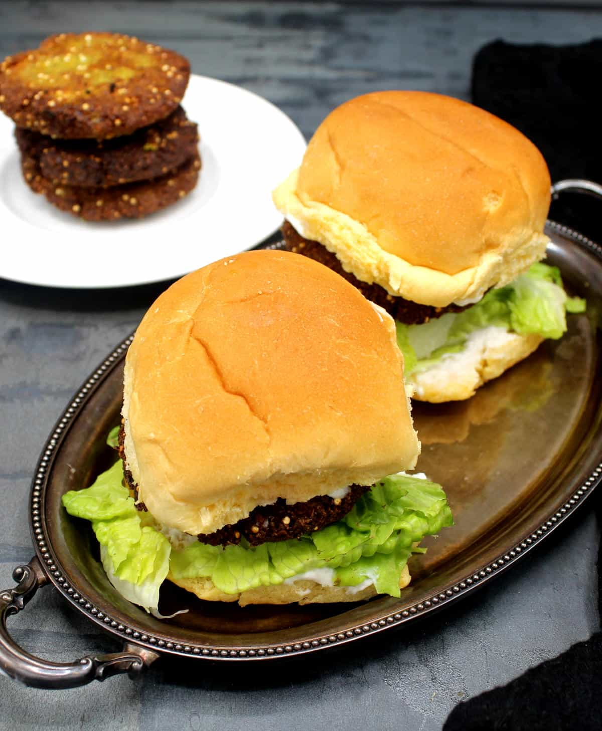 Photo of two falafel burgers on a silver tray with lettuce and vegan mayo and more falafel burger patties on a white plate in background.